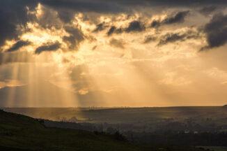 Beams of golden light across Flodden Moss from the Campsie Fells after a storm